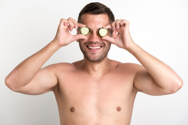 Young shirtless smiling man covering eyes with cucumber slice standing against white wall