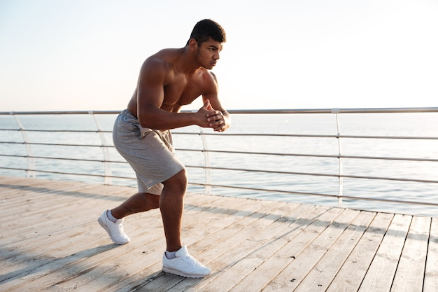 Young shirtless sportsman doing squats on the pier in the morning