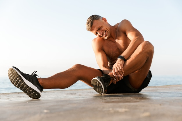 Young shirtless sportsman suffering from an ankle pain