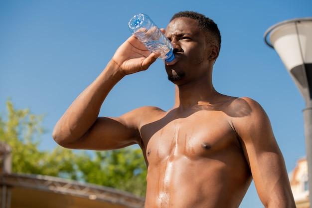 열심히 훈련 후 푸른 하늘과 녹색 단풍에 서있는 동안 병에서 젊은 벗은 목 마른 스포츠맨 마시는 물