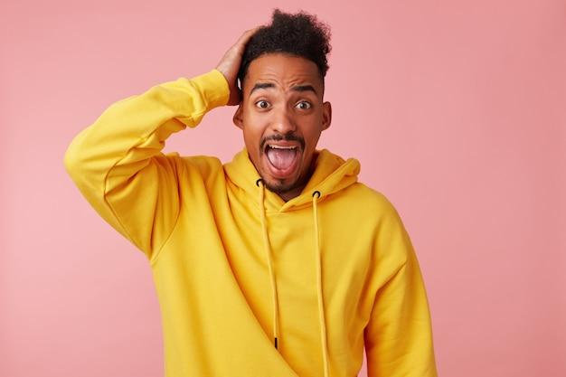 黄色いパーカーを着た若いショックを受けたアフリカ系アメリカ人の男は、頭を抱え、大きく開いた目と口で驚いておびえているように見えます。