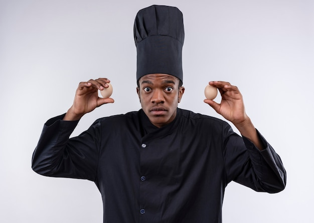 Young shocked afro-american cook in chef uniform holds eggs on both hands  isolated on white wall