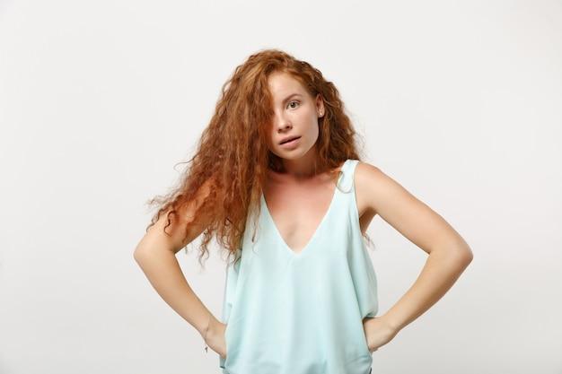 若いショックを受けた怒っている赤毛の女性の女の子は、白い背景、スタジオの肖像画に分離されたポーズをとってカジュアルな明るい服を着ています。人々のライフスタイルの概念。コピースペースをモックアップします。腰に腕を腰に当てて立っている。