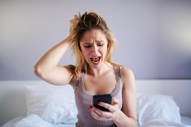 Young shocked attractive blonde sitting in bedroom and looking at disturbing message on smart phone