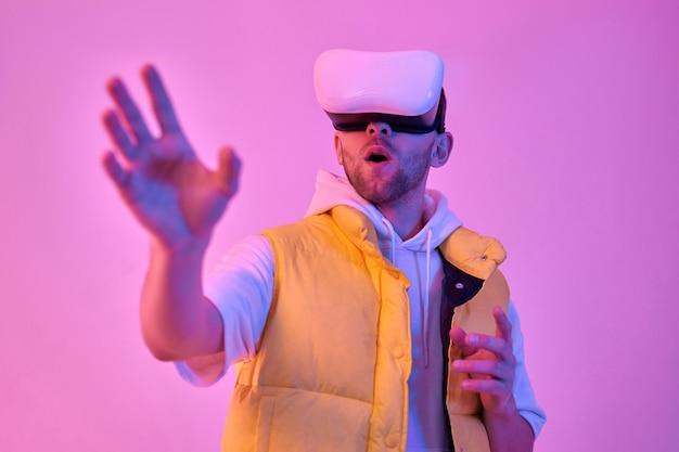 カジュアルな服を着た若いショックを受けた魅力的な男は、仮想現実のメガネを使用して、ネオンピンクで隔離された彼の手で何かに触れようとしています