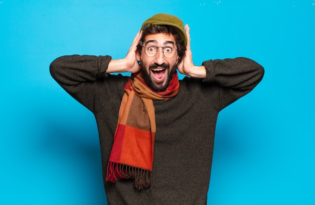 Young shocked bearded man wearing hat and scarf