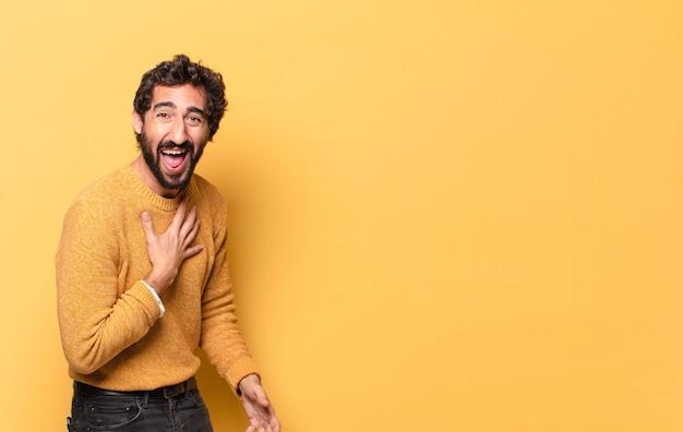 Молодой шокированный бородатый мужчина с желтым свитером