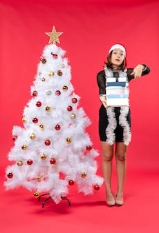 Giovane bella donna scioccata con cappello di babbo natale e in piedi vicino ai regali della holding dell'albero di natale decorato