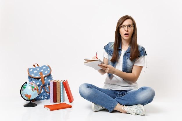 Giovane studentessa scioccata e sconcertata con gli occhiali che scrive note sul taccuino seduto vicino allo zaino del globo, libri scolastici isolati