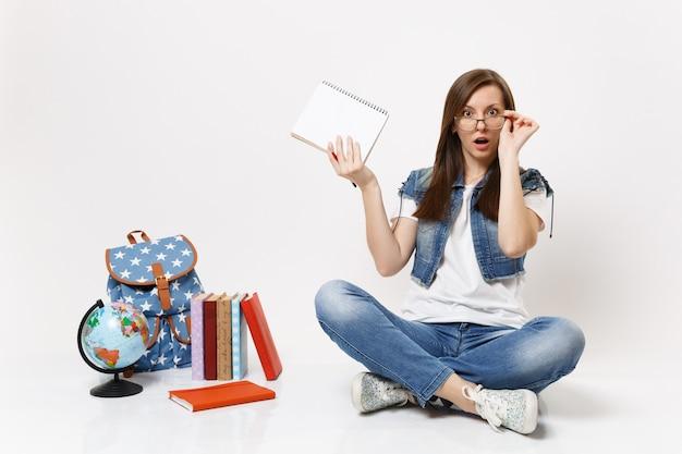 Giovane studentessa scioccata e sconcertata che tiene la mano sugli occhiali tiene un taccuino a matita seduto vicino allo zaino del globo, libri di scuola isolati