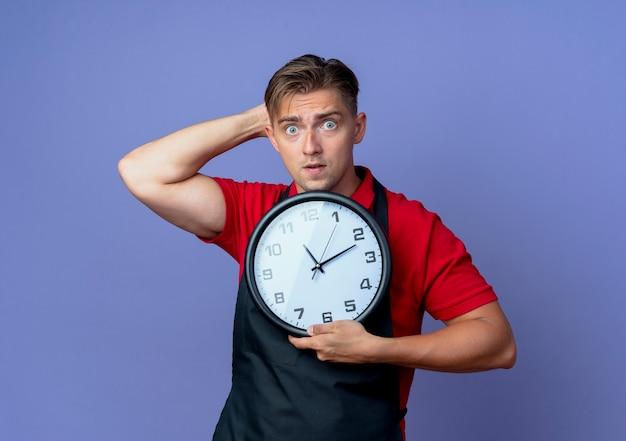 Il giovane barbiere maschio biondo scioccato in uniforme mette la mano dietro l'orologio della tenuta della testa isolato sullo spazio viola con lo spazio della copia