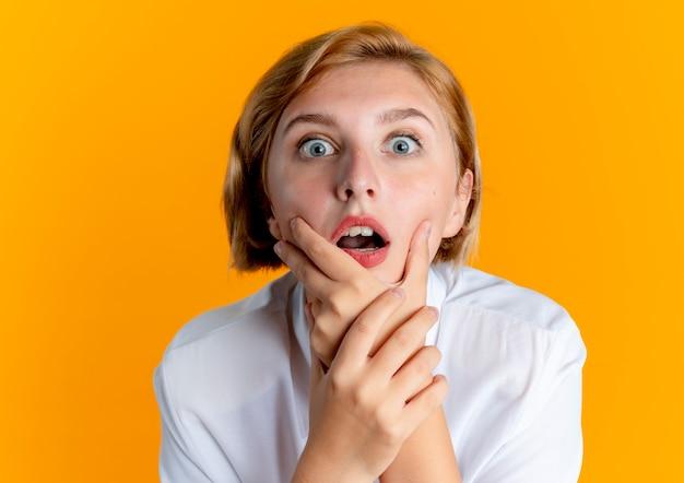 Молодая шокированная русская блондинка держит подбородок и смотрит в камеру