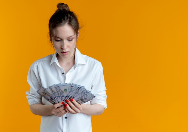 Young shocked blonde russian girl holds and looks at money isolated on orange space with copy space