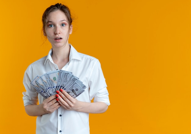 Young shocked blonde russian girl holds money isolated on orange space with copy space