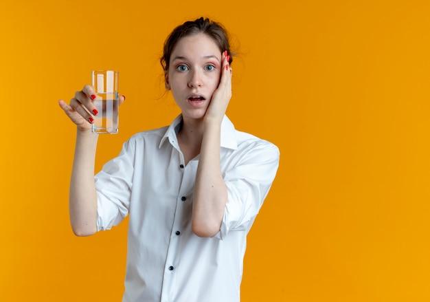 Молодая шокированная русская блондинка кладет руку на лицо, держа стакан воды на оранжевом пространстве с копией пространства