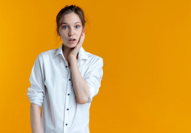 若いショックを受けた金髪のロシアの女の子は、コピースペースとオレンジ色のスペースで隔離の顔に手を置きます