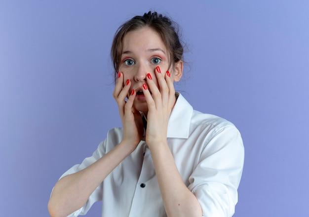 La giovane ragazza russa bionda scioccata mette le mani sul viso sulla viola con lo spazio della copia