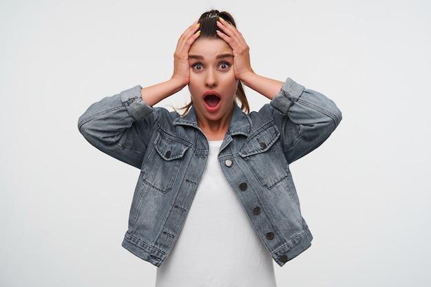La giovane signora bruna scioccata indossa una maglietta bianca e giacche di jeans, guarda la telecamera con la bocca e gli occhi spalancati, l'espressione sorpresa, tiene i palmi sulla testa, si erge su sfondo bianco.