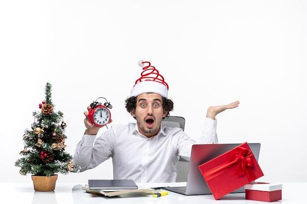 Молодой шокированный деловой человек в шляпе санта-клауса и показывает часы и сидит в офисе на белом фоне