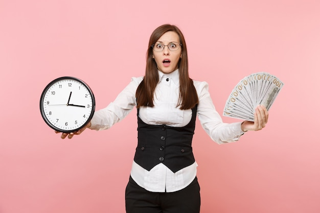 Young shocked business woman spreading hands holding bundle lots of dollars, cash money and alarm clock isolated on pink background. lady boss. achievement career wealth. copy space for advertisement.