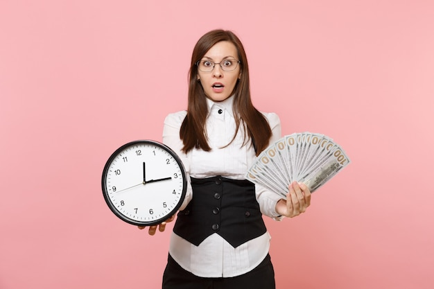 Young shocked business woman in suit glasses holding bundle lots of dollars, cash money and alarm clock isolated on pink background. lady boss. achievement career wealth. copy space for advertisement.
