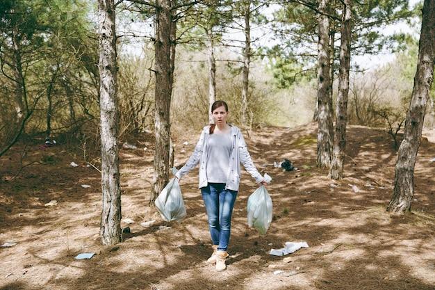 Молодая потрясенная обеспокоенная женщина в повседневной одежде держит мешки для мусора, убирая мусор в замусоренном парке или лесу. проблема загрязнения окружающей среды. остановить мусор природы, концепция защиты окружающей среды.