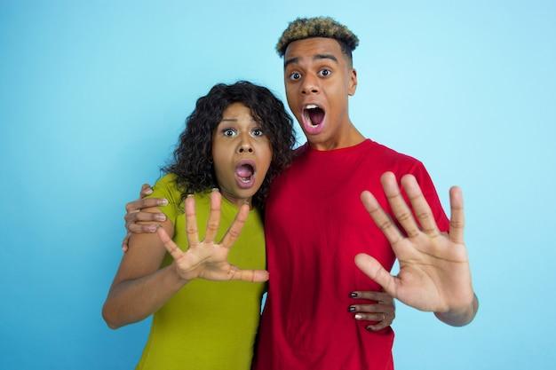 Giovane coppia scioccata in abiti casual in posa sulla parete blu