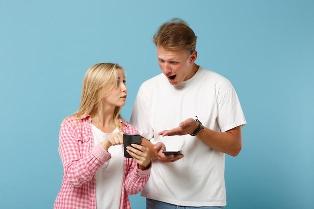젊은 충격 된 커플 친구 남자와 여자 화이트 핑크 빈 빈 티셔츠 포즈