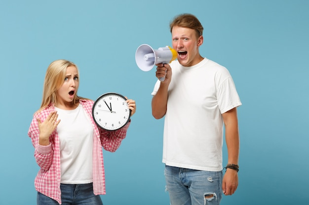 若いショックを受けたカップル2人の友人の男と女の白いピンクの空のtシャツのポーズ