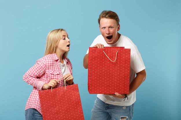 젊은 충격 된 커플 두 친구 남자와 여자 포즈 흰색 분홍색 티셔츠에