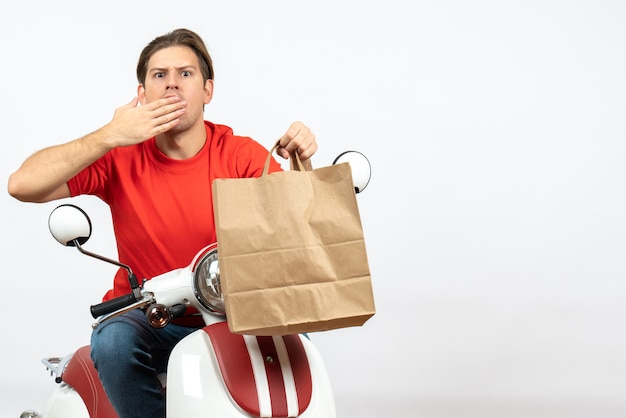 Young shocked courier guy in red uniform sitting on scooter holding paper bag and putting hand on his mouth on white wall