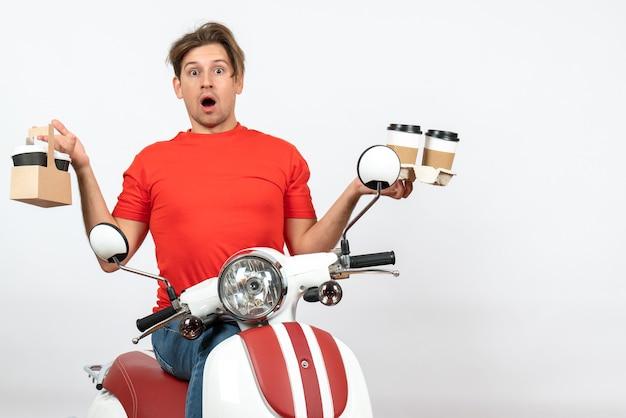 Молодой шокированный курьер в красной форме сидит на скутере и держит заказы на желтой стене