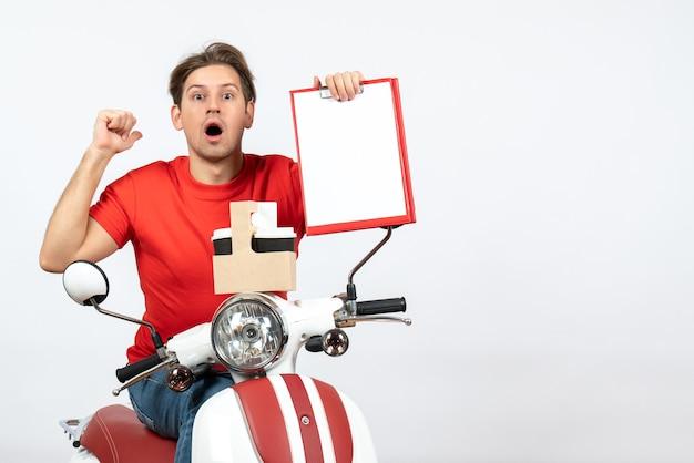Uomo giovane corriere scioccato in uniforme rossa che si siede sullo scooter che tiene ordini e documenti sulla parete gialla