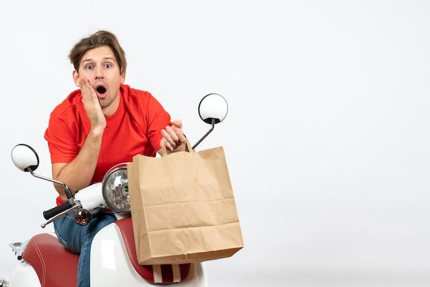 Giovane corriere scioccato uomo in uniforme rossa seduto su scooter tenendo il sacchetto di carta sulla parete gialla