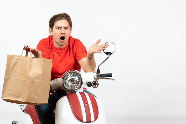 Giovane ragazzo di consegna scioccato in uniforme rossa che si siede sul motorino che tiene il sacchetto di carta sul muro bianco