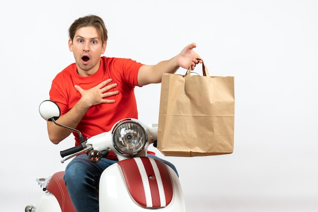 Young shocked delivery guy in red uniform standing near scooter giving paper bag to someone on white wall