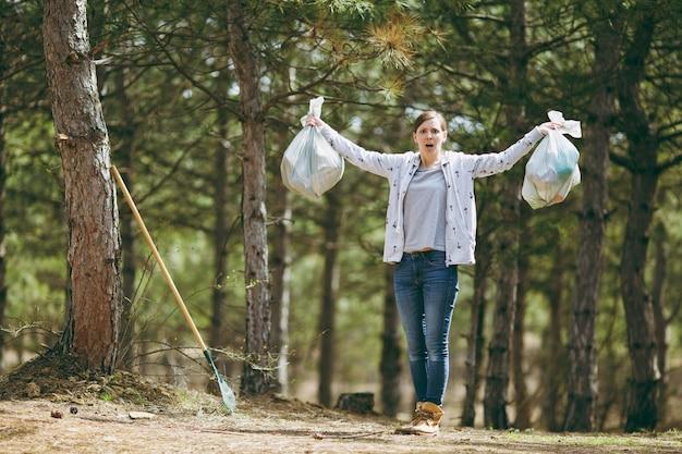 젊은 불만 불만 여자가 공원에서 쓰레기 봉투와 함께 손을 퍼뜨리는 쓰레기를 청소합니다. 환경오염 문제