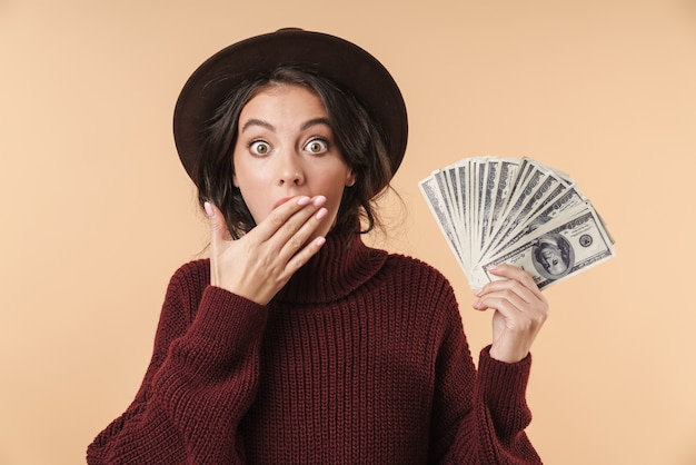 Молодая потрясенная эмоциональная брюнетка женщина, изолированная над бежевой стеной, держащей деньги, прикрывающие рот.