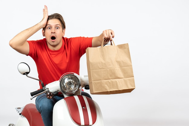 Young shocked emotional courier guy in red uniform sitting on scooter holding paper bag on white wall