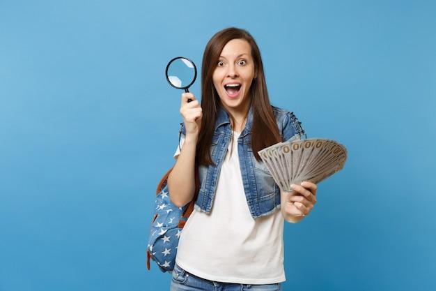 젊은 여대생은 배낭을 메고 많은 달러 현금 돈을 들고 파란색 배경에 격리된 지폐를 확인하는 돋보기를 들고 충격을 받았습니다. 돈의 진위 여부 확인.