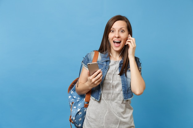 젊은 충격을 받은 흥분한 여학생은 배낭을 메고 입을 벌리고 이어폰을 들고 파란색 배경에 격리된 휴대전화를 들고 음악을 듣습니다. 고등학교에서 교육입니다. 광고 공간을 복사합니다.