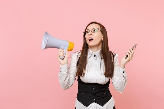 Молодые потрясены измученной деловой женщиной в костюме, очках, глядя вверх, держа мегафон и мобильный телефон, изолированные на розовом фоне. леди босс. достижение карьерного богатства. скопируйте место для рекламы.