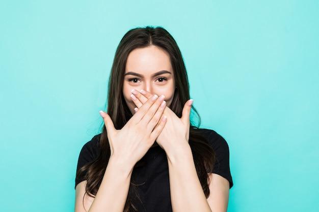 若いショックを受けた少女はターコイズブルーの壁に隔離された手で口を覆う