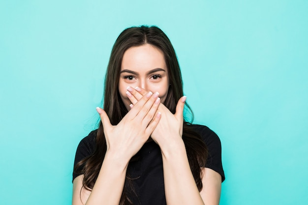 Young shocked girl cover mouth with hands isolated on turquoise wall
