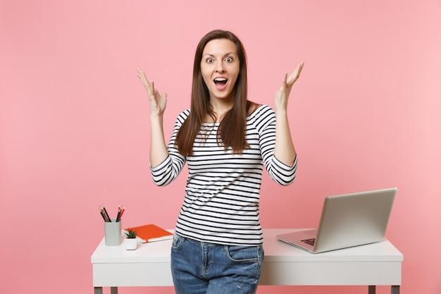 パステルピンクの背景に分離されたpcラップトップと白い机の近くに立って手を広げてカジュアルな服を着てショックを受けた少女。業績ビジネスキャリアコンセプト。広告用のスペースをコピーします。