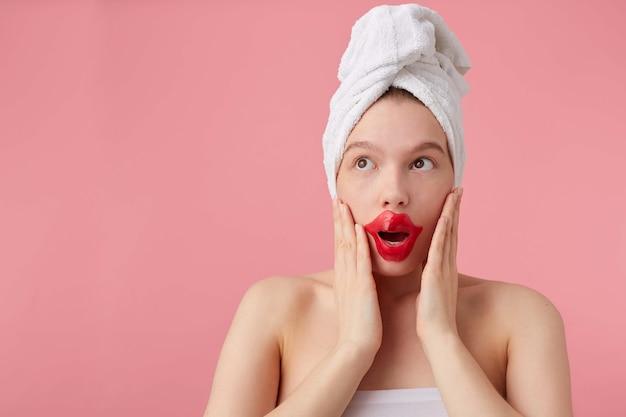 スパの後、頭にタオルと唇のパッチを当ててショックを受けた若い女性は、目を大きく開いて目を離し、新しいゴシップを聞き、手のひらで頬に触れ、立ちます。