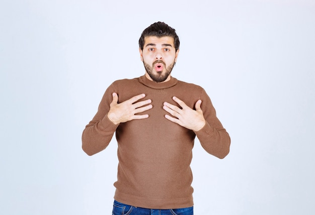 Young shocked man putting his hands on chest isolated on a white wall.