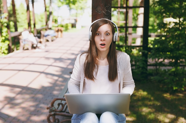 Young shocked pretty businesswoman in light casual clothes. woman working on modern laptop pc computer, listen music in headphones on head in street outdoors. mobile office. freelance business concept