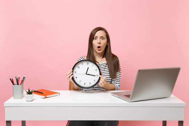 Young shocked puzzled woman holding round alarm clock while sit work at office with pc laptop
