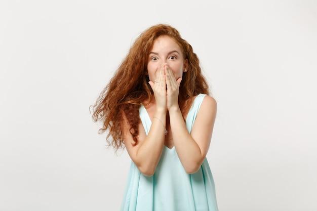 若いショックを受けた赤毛の女性の女の子は、白い背景のスタジオの肖像画に分離されたポーズをとってカジュアルな明るい服を着ています。人々の誠実な感情のライフスタイルの概念。コピースペースをモックアップします。手で口を覆う。